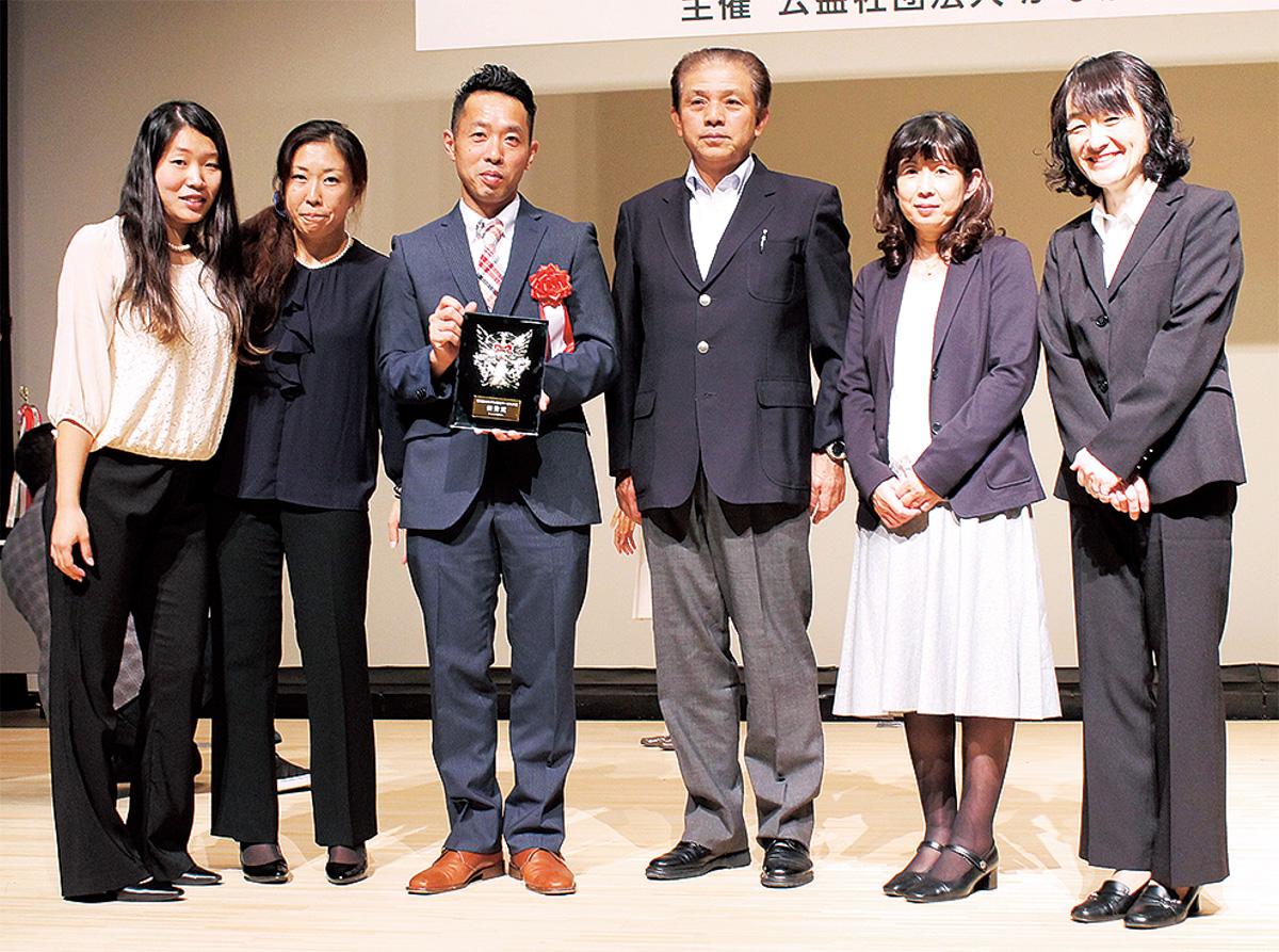 授賞式でのプロジェクトメンバー。「将来は特別なカフェや居場所がなくてもすべての地域ですべての人々が共存できる当たり前の生活環境づくりをめざします」とリーダーの幸田裕介さん(左から3番目)