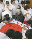 応援旗への署名を集める上崎さん目標は1000人と話す