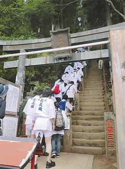 門を開けて山頂への階段を登るお花講(昨年)