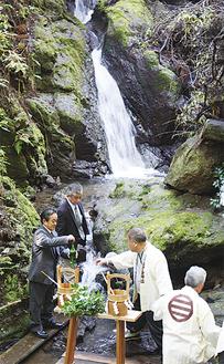三段の滝で御神水をくむ参列者