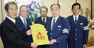 カバーを手渡す上林会長(右から2番目)