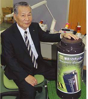 開発した地すべり検知器を手にする遠藤社長