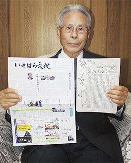 会報の創刊号と最新号を手にする野崎会長