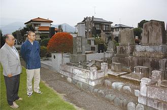 大橋本家の駒形墓碑を眺める林会長(左)と岩田住職