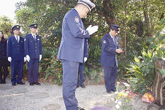 墓前に手を合わせる警察署員たち