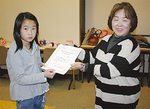 梅都会長から賞状を受け取る佐川さん(左)