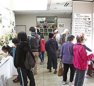 展示された作品を眺める来場者(南公民館で14日)