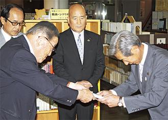 高山市長に「世界」を渡す市川会長(左)