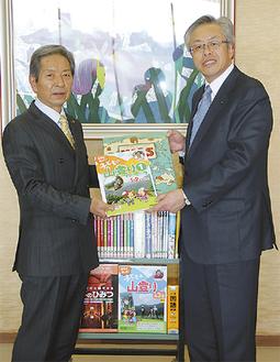 高山市長に本を手渡す鶴井常務理事
