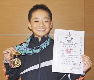 メダルと賞状を手に笑顔の添田君