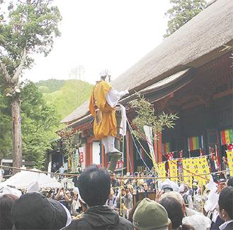 シイの木に登り参拝者の安穏平安を願う