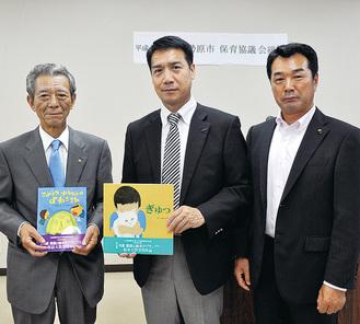 石井会長(左)に絵本が手渡された