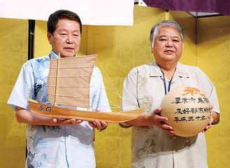 記念品として贈られた「鮎まつり」を象徴する花火玉のレプリカを持つ上原市長(右)と、帆掛け船「サバニ」の模型を手にする小林市長