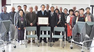 寄贈した椅子を前に感謝状を手にする増田健治代表取締役