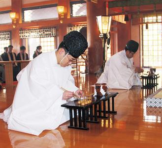 「米(わせ・なかて・おくて)」や「ごま」、「いも」など農作物が書かれた竹筒で粥を掬う神職