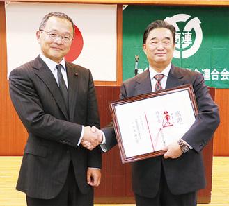 握手を交わす山田前会長(右)と大山新会長=5月14日伊勢原シティプラザで写す