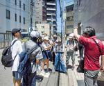 水島教授(右)の案内で爆心地を見学する中学生(提供写真)