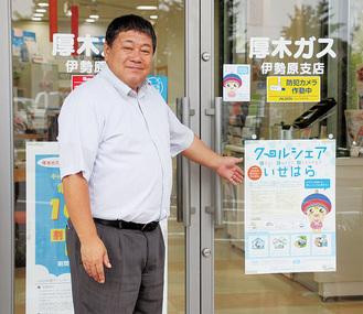 厚木ガス(株)伊勢原支店ショールームの入口に立つ、飯塚支店長。登録施設はポスターやステッカーが目印