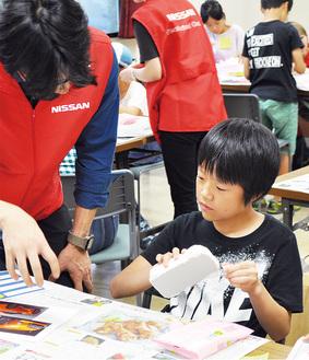 写真を参考に紙粘土を成型する参加者
