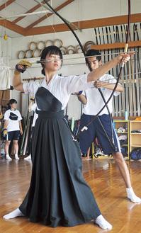 集中力を高めて弓を弾く米山さん(手前)