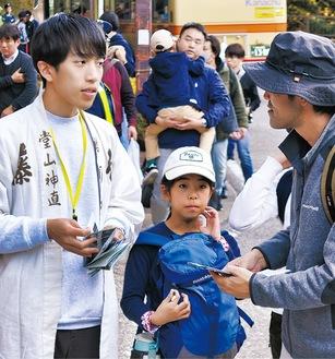 観光客にスタンプラリーを説明する井上さん(左)