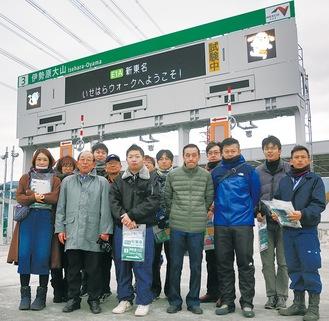 同社が手がけた道路情報板の前に立つ社員ら。前列左から2番目が大田社長=12月7日に写す