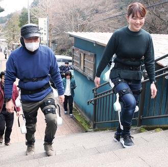 ロボットを装着してこま参道の階段を上がる参加者