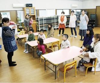 保育士(左)の指導のもと、遊びを通して集団生活を学ぶ子どもたち=八幡台集会所
