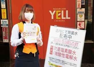次亜塩素酸水のペットボトルとチラシをもつスタッフ。マスクと手袋の着用を徹底している