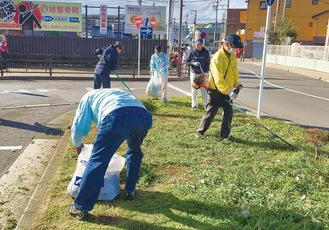 愛甲石田駅前ロータリー広場で草刈りや清掃活動をする会員ら(写真提供=同委員会)