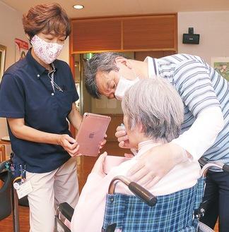 タブレット端末を使って、ビデオ通話で磨き方のアドバイスを受ける介護福祉士ら=ローズヒル