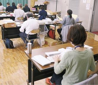 郵送申請用の書類を封入する市職員ら=5月18日、市民文化会館