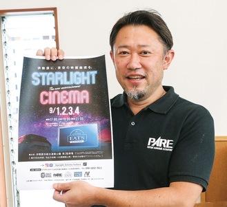 ポスターを手にする実行委員長の中村さん