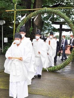 茅の輪をくぐり、大祓式に向かう神職ら