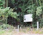道路わきの竹林の入り口にある解説板(奥に墓石が並ぶ)