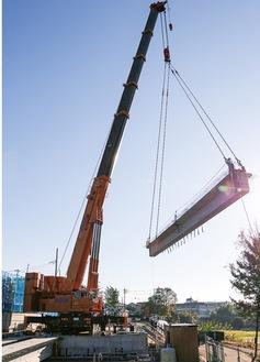 大型クレーンで重さ約50tの橋げたを設置する架設作業=12月7日に写す