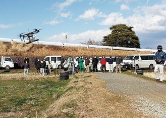 農業用ドローン(左)の操縦を見守る関係者ら