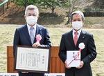 感謝状を手にする吉田代表取締役(左)