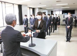 高山市長(手前)から辞令を受け取る新採用職員の代表者