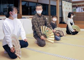 講師の松木さん(左から2番目)から扇子の扱い方を習う子どもたち=大山阿夫利神社社務局