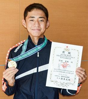 メダルと賞状を手にする添田さん