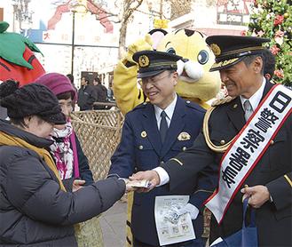 通行者に防犯グッズを配布する渡辺さん(写真右)