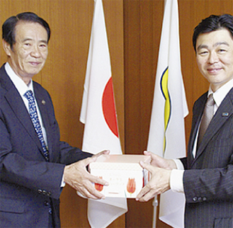 笠間市長へ寄贈する服部支配人(右)