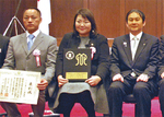 表彰式で盾を手にする志澤社長(中央)