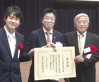 加藤勝信内閣府特命担当大臣(中央)と賞状を持つ渋谷委員長(左)
