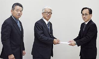 又吉住宅防音第1課長(右)に要望書を手渡す宮東会頭(中央)と笠間会長(左)