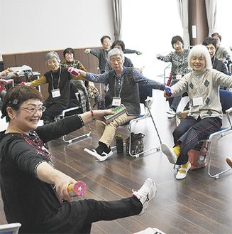 歌に合わせ楽しそうに体操する参加者。手前が講師で会の代表を務める吉川さん