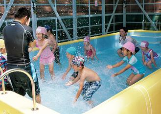 先生と水のかけっこをしてはしゃぐ園児たち