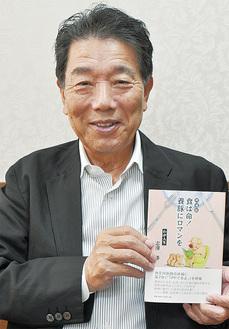 著書を手にする志澤会長