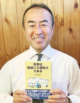 著書を手に笑顔を見せる坂井さん